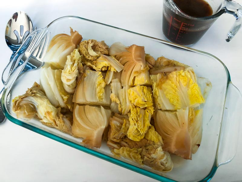 Instant Pot Beijing Style Hot and Sour Cabbage in a glass pyrex dish on a white tray with serving spoon and fork with sauce on the side