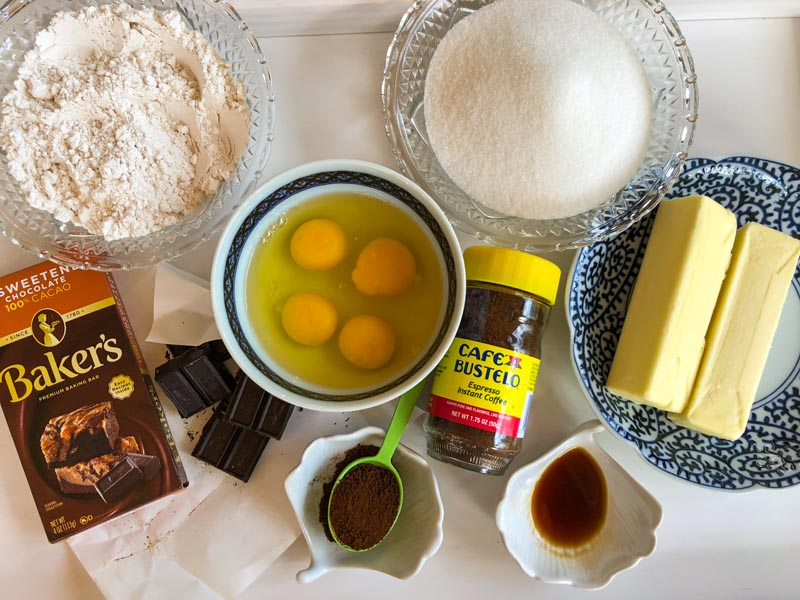 Espresso Brownie ingredients on a white tray. Four eggs our of their shells in a bowl. Small jar of instant espresso coffee, 1/2 pound of butter in a dish, bowlful of flour, bowlful of sugar, unsweetened Baker's chocolate squares, vanilla.