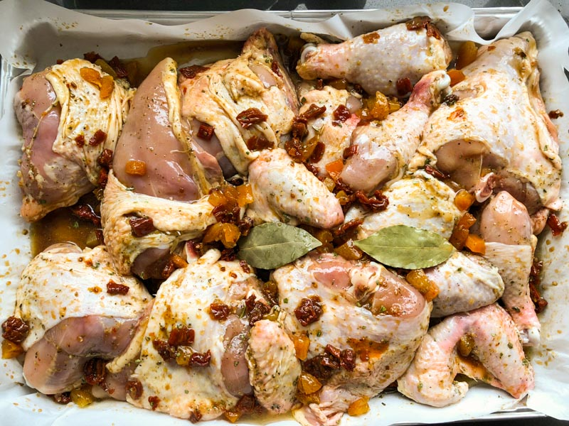 holiday chicken in roasting pan with marinade all around.