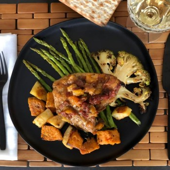 Black plate with Holiday Chicken, covered in gravy, on top or asparagus, roasted green cauliflower and roasted asparagus. matzah and white wine on the side. White napkin, bamboo placemat and black cutlery.