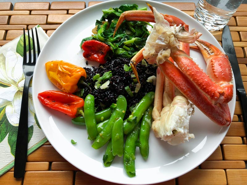 White dinner plate on a bamboo placemat with black cutlery. Cooked crab legs, snap peas, snow pea leaf shoots, roasted peppers and black rice are on the plate. Glass of water on the side