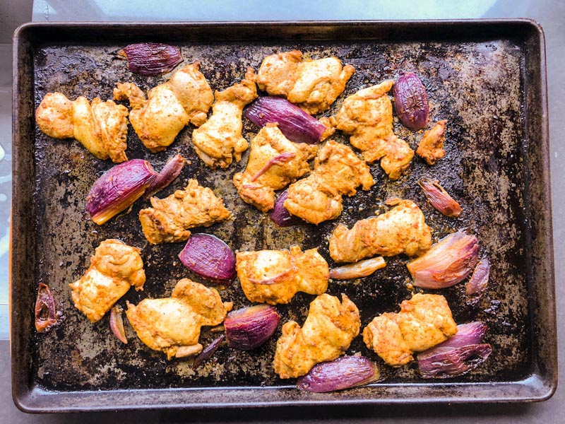 oven-roasted chicken shawarma: Cooked marinated chicken thighs and red onions on sheet pan, straight out of the oven