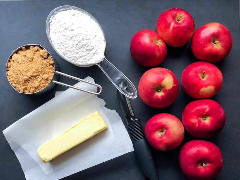 Apple crisp ingredients on a black cutting board