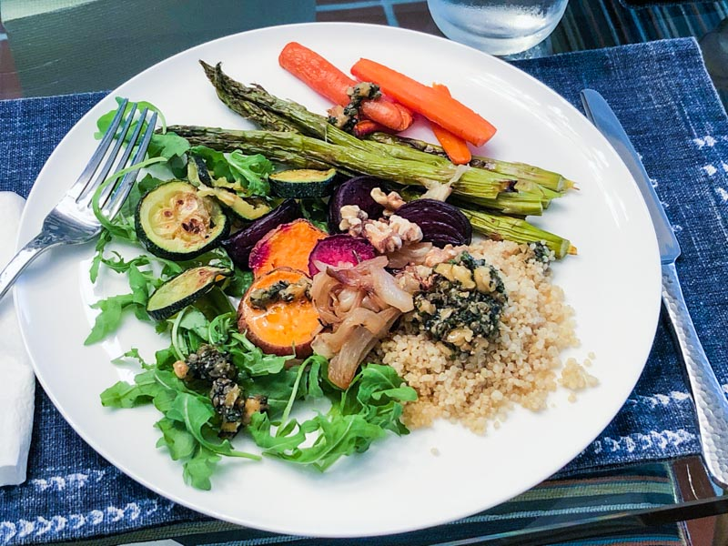 Quinoa Roasted Veggie Salad with Gail's Caper-Walnut Vinaigrette on a white plate with a blue and white placemat