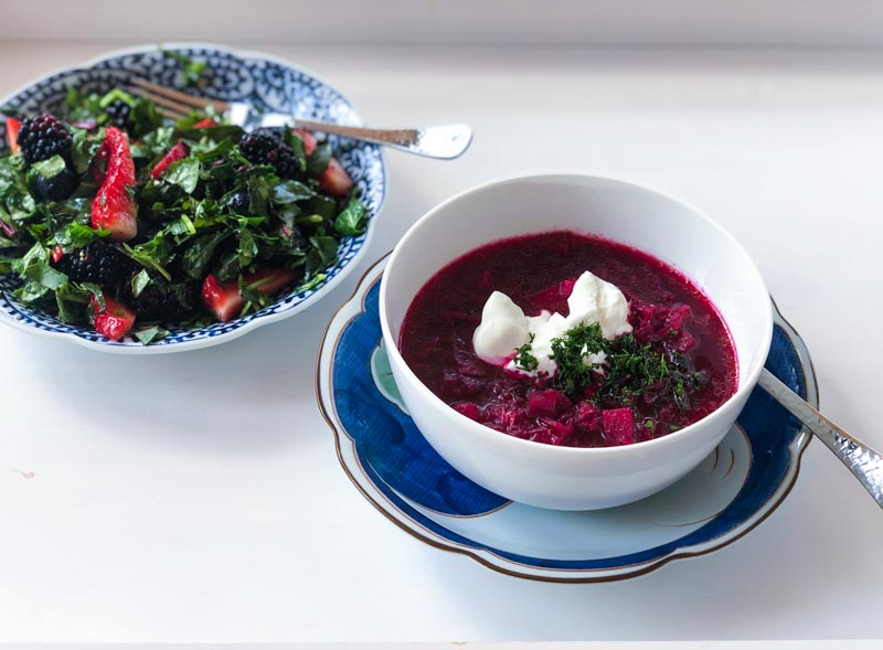 Russian Borscht soup in a white bowl on a blue and white plate, on a white tray, with a beet green, kale, berry salad.