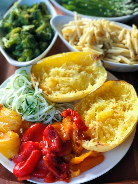 Roasted Spaghetti Squash Pesto Pasta Bar ingredients cooked on white dishes on a wooden tray