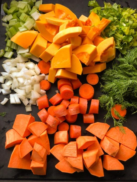 Ingredients for Carrot Squash Sweet Potato Soup, cut in chunks on a black cutting board. Includes onion, celery, celery leaves and dill