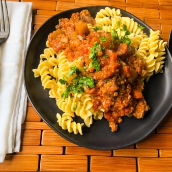 Pasta Bolognese with Lentils served over rotini on a black plate.
