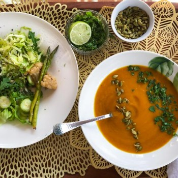 Instant Pot Ginger Lime Squash Soup in a white bowl, garnished with cilantro and pumpkin seeds, a bowl of salad on the side.
