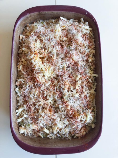 Cooked vegetables in casserole dish, cauliflower, carrots and leeks, cut into chunks and covered in Cheddar cheese sauce, topped with bread crumbs, then cheese and paprika sprinkled on top