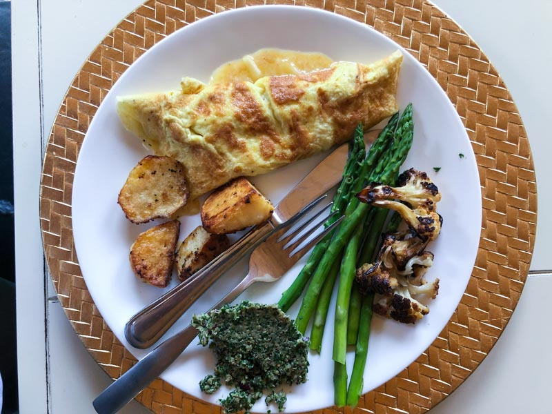 Parsley salad on a plate with a Cheddar cheese omelet, asparagus, roasted cauliflower and roasted potatoes