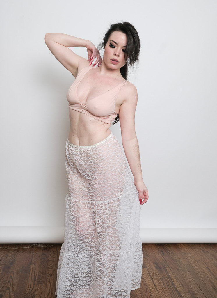 Jasmin Jai stands wearing a long lace skirt, hair in a ponytail, looking down with her hand up on her shoulder