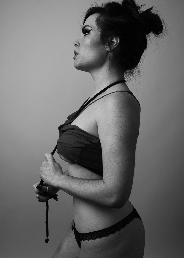 Profile black and white shot of Jasmin Jai holding Rope Bondage around her neck and under breast coming out of her top with panties on