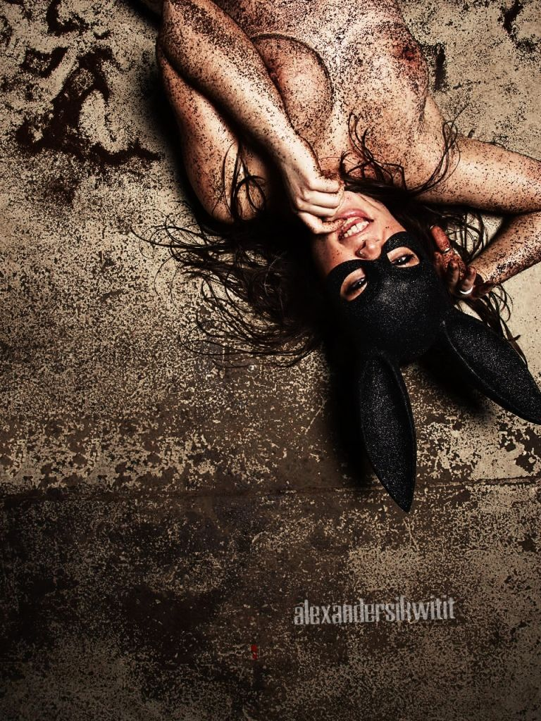 Jasmin Jai wearing a bunny mask laying on the floor, her body covered in coffee grounds