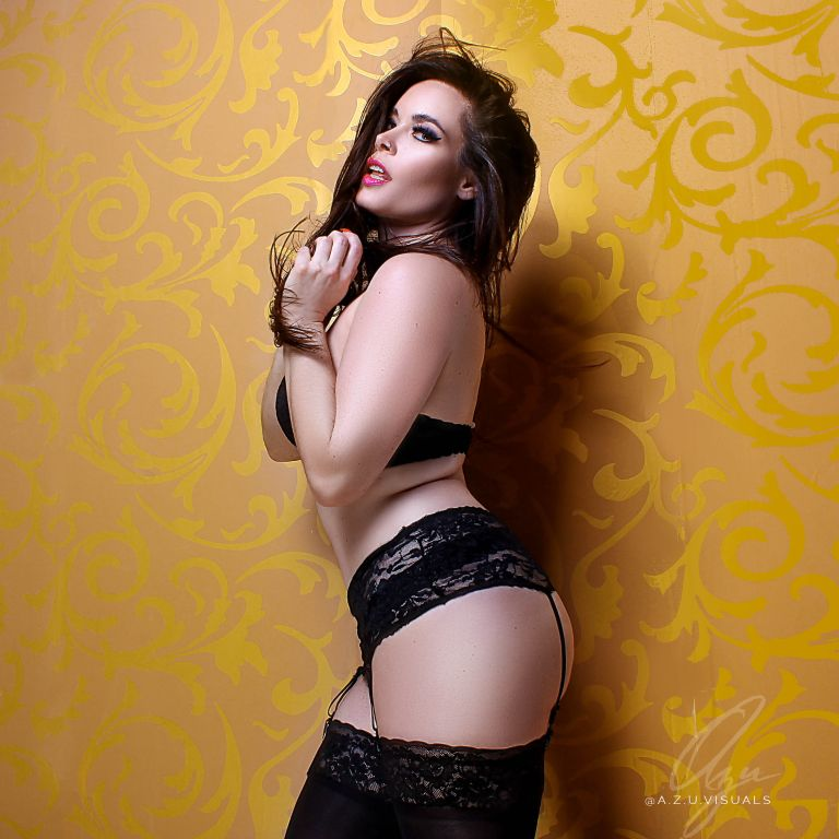 Jasmin Wearing a Garter Belt, Thigh Highs against a Gold Wall