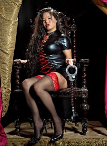 Mistress Alexis kim sits upon a wooden thrown in a shiny dress and thigh highs. She dangles your handcuffs in front of her.