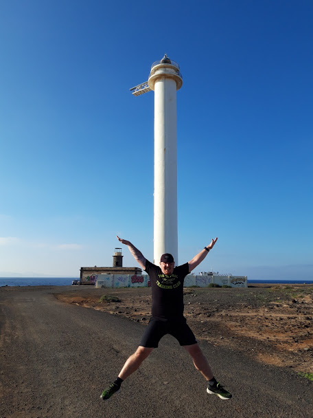 Runner jumping in front of Faro de Pechiguera lighthouse
