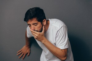 Portrait of young man drunk or sick vomiting