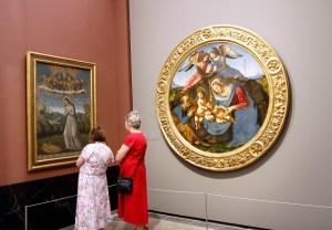 Twee dames zijn erg onder de indruk van het schilderij.