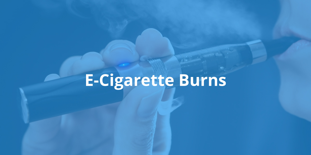 """Closeup of a hand holding a smoking e-cigarette being held up to a woman's lips, tinted blue, with the words """"E-Cigarette Burns"""" in white font in the middle."""