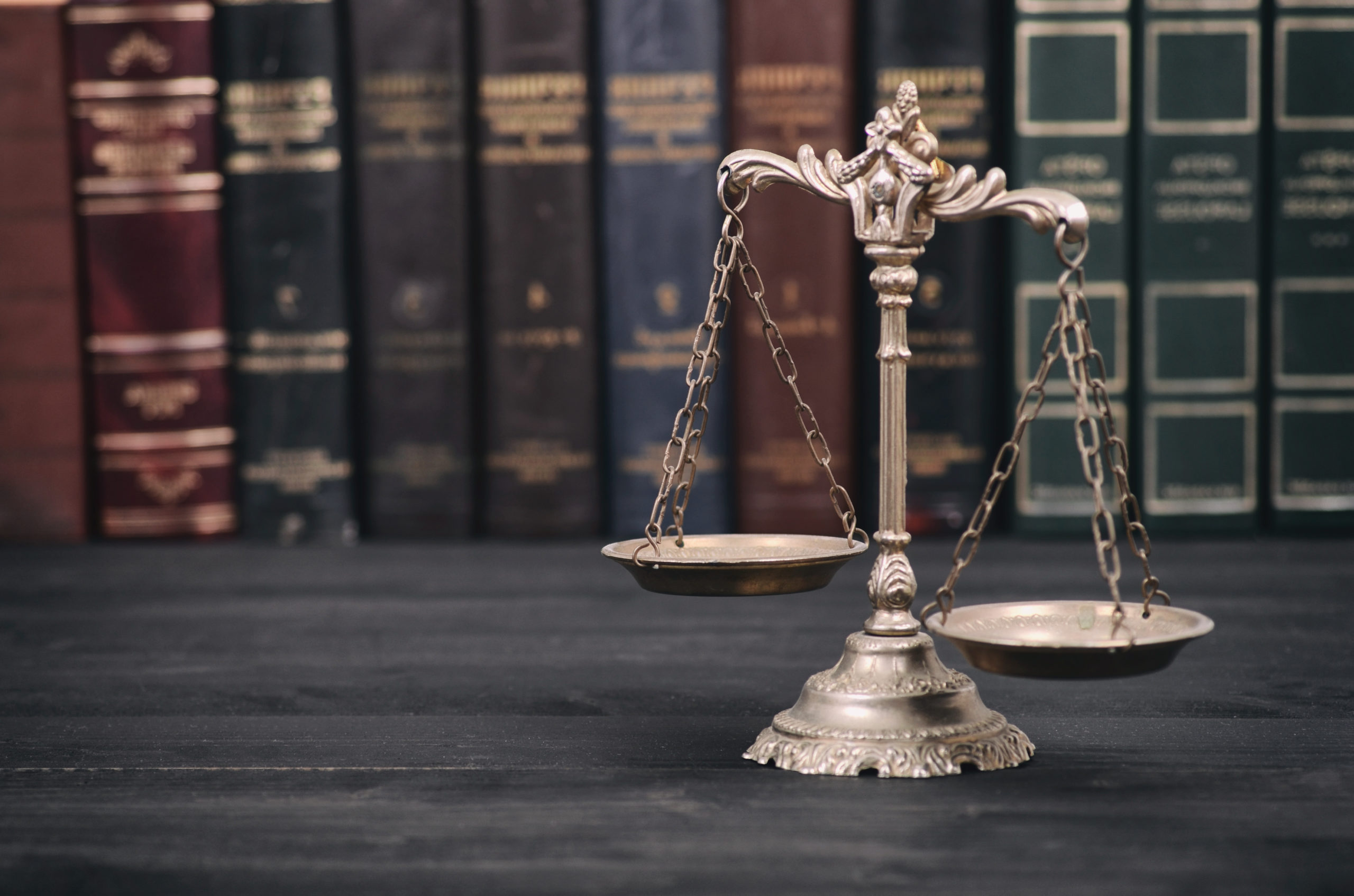 Closeup photograph of a scales of justice in a light gold sitting on a black wooden surface, with hardbound legal reference books with gold lettering in the background.
