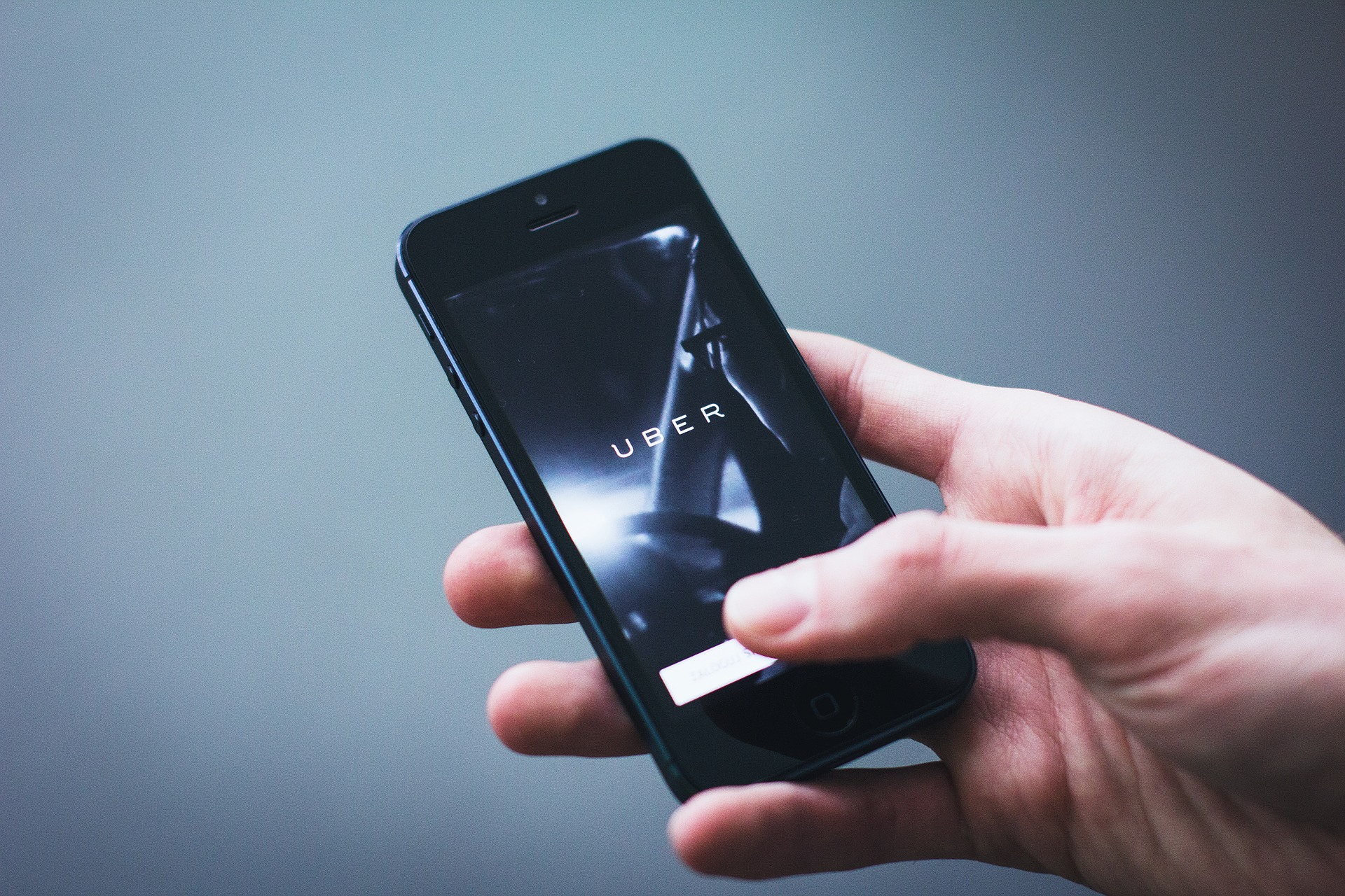 Closeup of a caucasian and holding and iPhone with the Uber App open, symbolizing the need for a liability lawyer in personal injury cases.