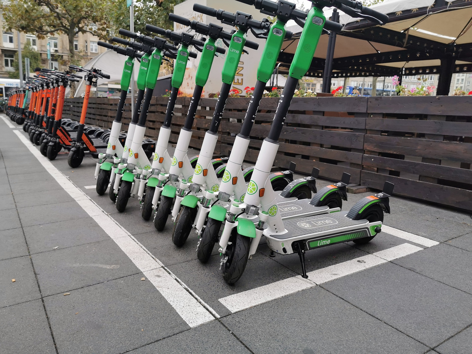 Large photo of 20+ green and red scooters parked in front of a restaurant with a brown, slatted, wooden fence, meant to symbolize the need for an accident lawyer and personal injury lawyer.