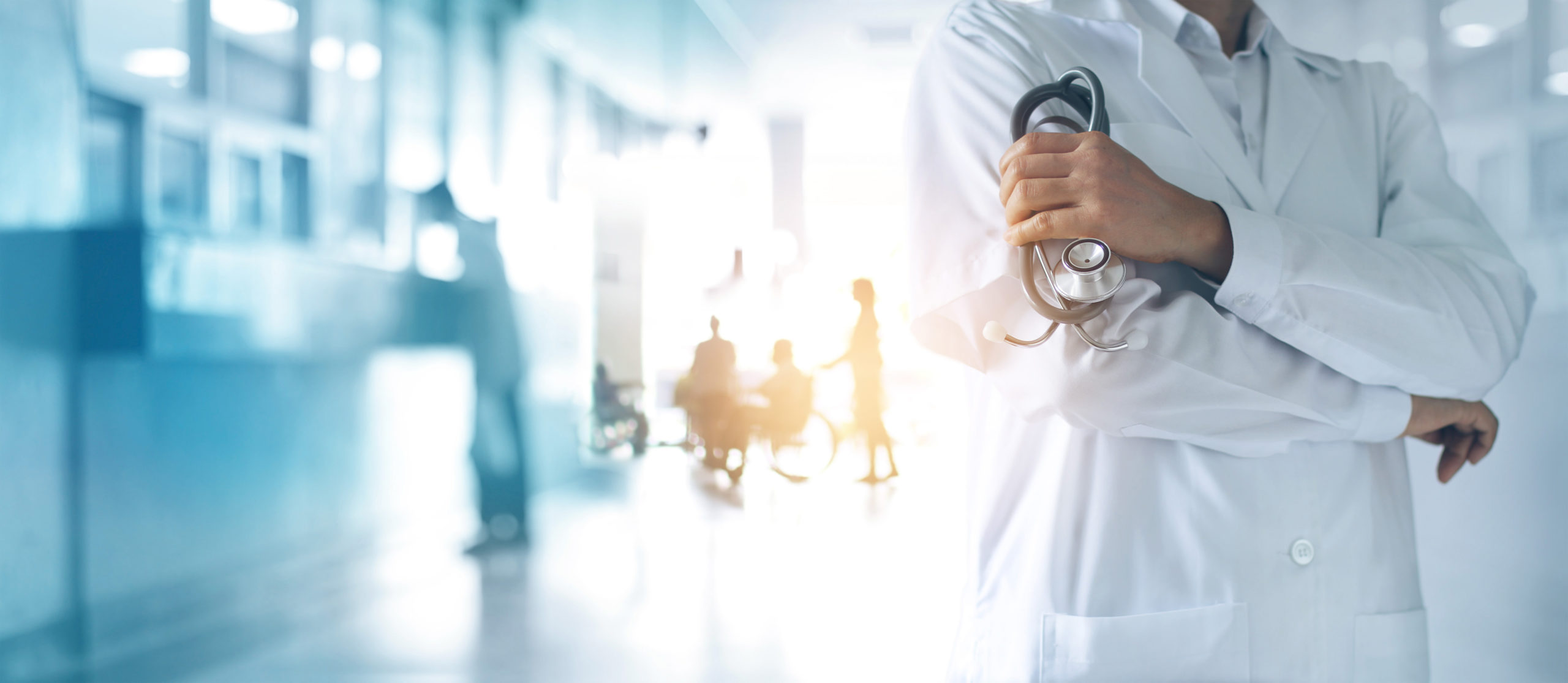 Neck-down photo of a doctor wearing a white coat, crossing his arms and holding a stethoscope in his left hand, symbolizing medical malpractice attributed to Covid-19. There are patients and staff blurred in the background.