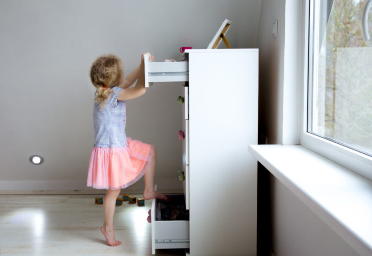 Large photograph of a female toddler girl climbing on a white dresser not affixed to the wall, symbolizing the importance of securing furniture, safety recalls, and tip-over lawsuits.