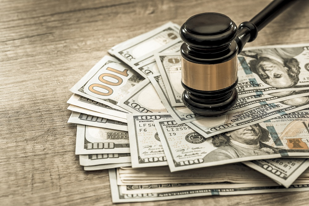 A gavel sits on top of a pile of $100 dollar bills on a wooden table, asking the question, How much to ask for in a personal injury settlement?