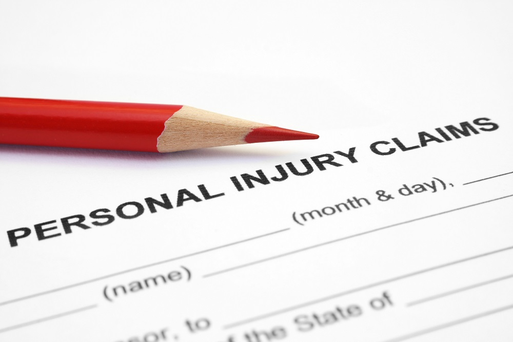 Closeup of a black and white personal injury case claim form, titled Personal Injury Claims, with a red colored pencil above the title, posing the question, What is personal injury on Philadelphia, PA?