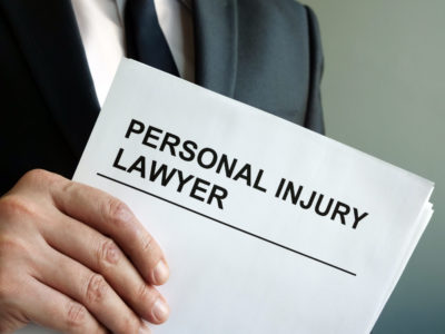 A man from the chest down, wearing a blue suit, white shirt, and blue tie holds a white paper that says PERSONAL INJURY LAWYER in capital letters and black font, posing the question, Do I need a personal injury lawyer in Philadelphia?