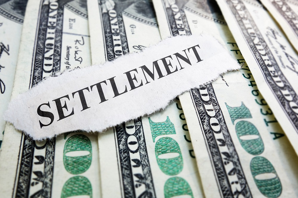 A torn white piece of paper with the word SETTLEMENT in all black caps sits on hundred dollar bills arranged vertically overlapping each other and showing the 100 at the bottom, posing the question, How Are Personal Injury Settlements Paid Out?