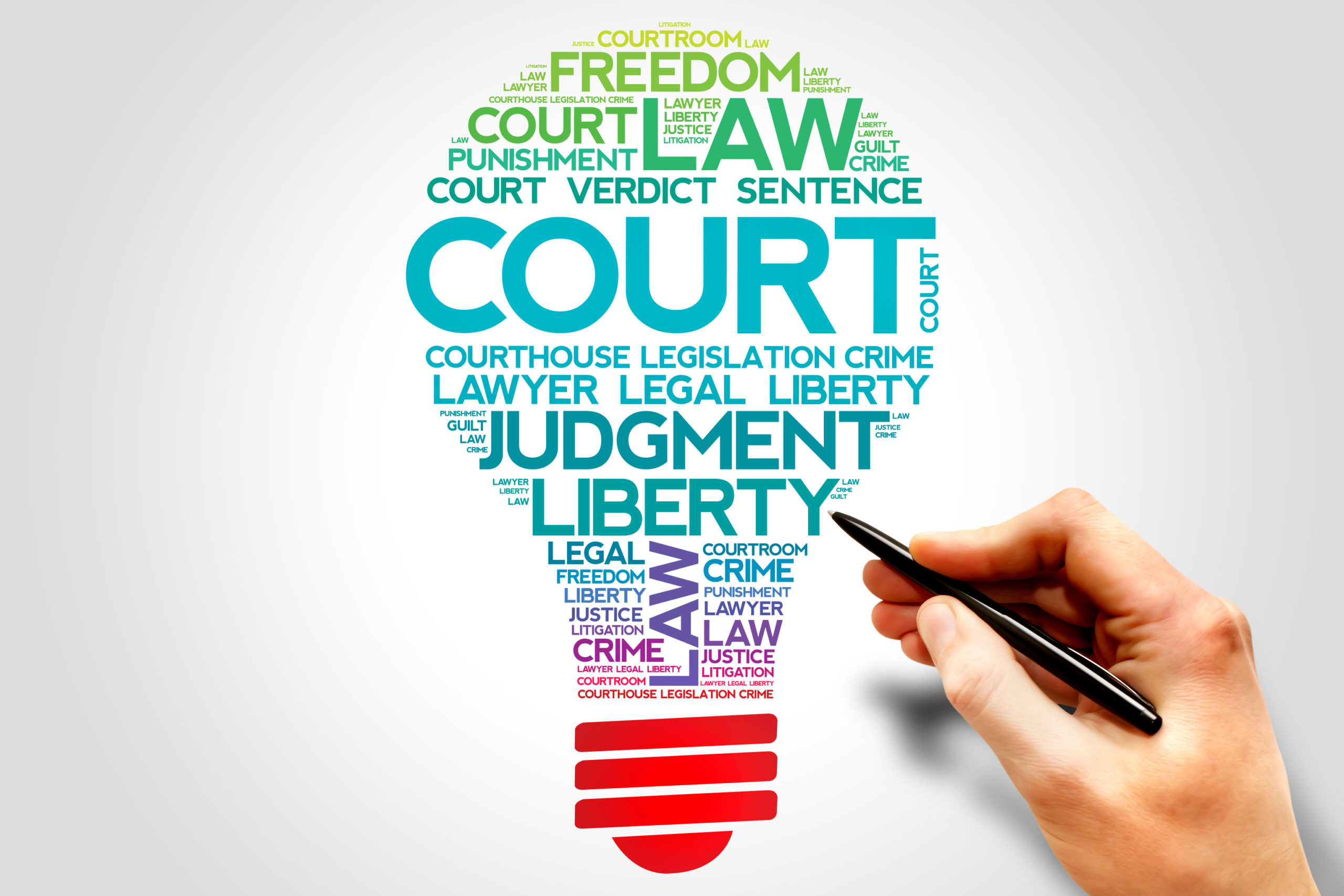 A hand holding a pen next to a colorful set of words like COURT, LAW, JUDGEMENT, LIBERTY and other related terms, arranged in the shape of a lightbulb, posing the question, What is a personal injury lawyer in Philadelphia?
