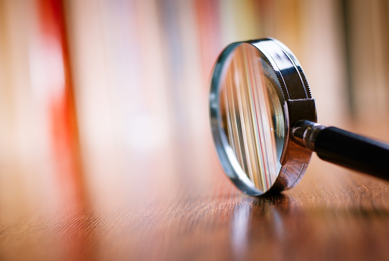 A magnifying glass on the right side of the image, the rim resting on a medium colored wood grain table so that the glass is upright, with the handle pointing to the right, symbolizing things to look for in a Philadelphia personal injury attorney.