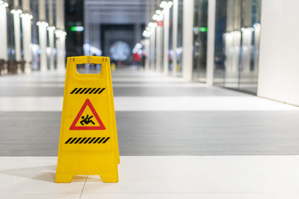 A yellow caution wet floor folding sign in the forefront and on the left, in front of a long broad walkway of smoot grey and white flooring, posing the question, What to do after a slip and fall accident in Philadelphia.