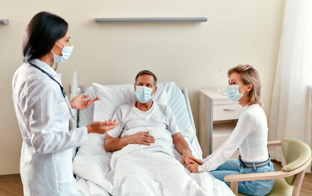 A man recovering from a personal injury in Philadelphia laying in a hospital bed wearing a mask and holding his wife's hand, who is also wearing a mask. A female doctor stands nearby wearing a mask and answerin gthe man's question, Will COVID-19 impact your personal injury case in Philadelphia?