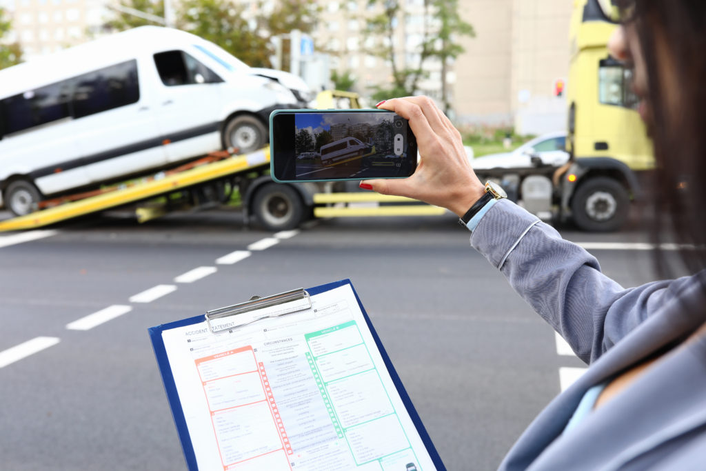 A woman's hand holds a phone out from the right side of the image, to take a picture of a white truck being loaded on to a tow truck in the distance. In the foreground a clipboard with a checklist can be seen, posing the question, will your truck accident case settle in Philadelphia?