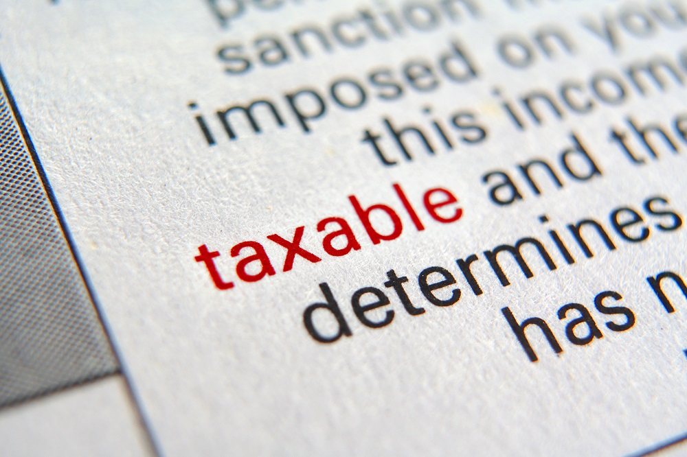 Closeup of a dictionary page angles to the left, focusing on the word TAXABLE in red lettering surrounded by its definition in black lettering, positing the question, Is a personal injury settlement taxable in Philadelphia?