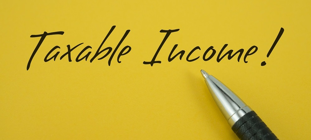 On a mustard yellow background TAXABLE INCOME! is written in black handwriting, above a silver tipped, back rubber grip pen, posing the question, Is a personal injury settlement taxable in Philadelphia?