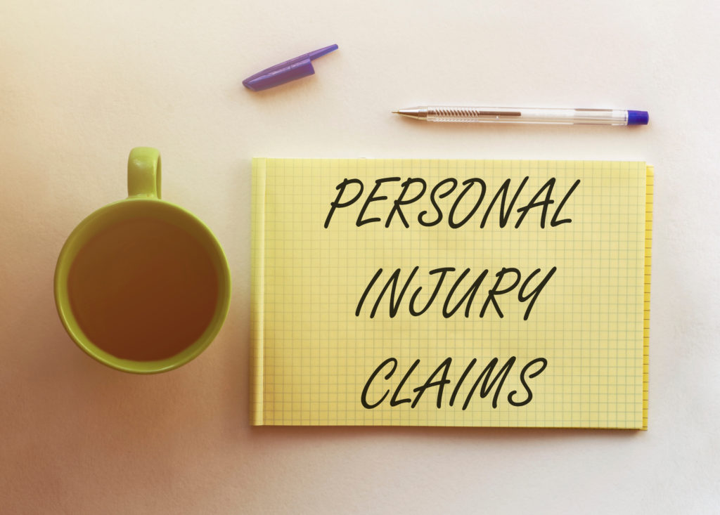 A coffee cup, purple and clear pen, and purple pen cap placed next to a yellow paper tablet that reads PERSONAL INJURY CLAIMS, posing the question, What is a personal injury claim in Philadelphia?