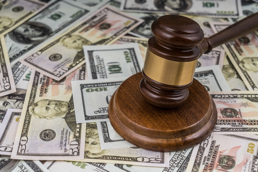 A wooden gavel with a gold accent is hitting a block placed on a table covered in 50 and 100 dollar bills, posing the question, How Much Do Personal Injury Lawyers Charge in Philadelphia?