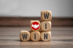 6 small wooden building blocks arranged so that WIN is spelled both vertically and horizontally, with the extra block with a picture of two white hands shaking against a circular red background on top of the 2nd column, symbolizing how to win your personal injury claim in Philadelphia.