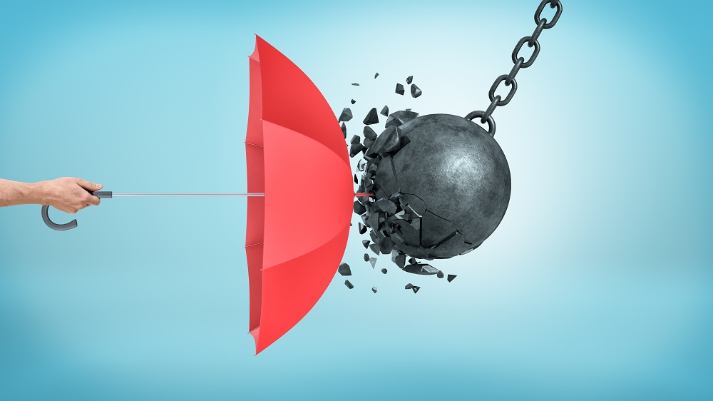With a cerulean blue background, a hand on the left holding a bright red umbrella sideways as a black ball hanging on a chain breaks as it hits the umbrella, posing the question, What does personal injury protection cover in Philadelphia?