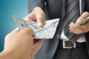 A man in a dark suit, white shirt, and striped grey tie hands money to a pair of receiving hands, posing the question, What is the average payout for a personal injury claim?
