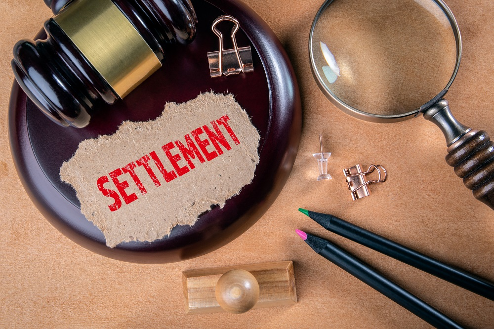 A light grained wood desk with a magnifying glass, pens, a stamp, binder clips, a dark wood and gold block and gavel, and a brown piece of paper with the word SETTLEMENT written in red, capital letters. The scene poses the question, What is the average settlement for a personal injury case in Philadelphia?