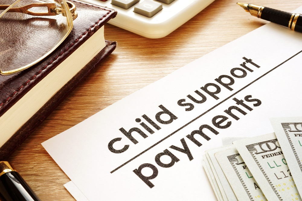 A white paper titled CHILD SUPPORT PAYMENTS with dollar bills placed on a light-grained wood desk, posing the question, Can Child Support Be Taken from a Personal Injury Settlement in Philadelphia?