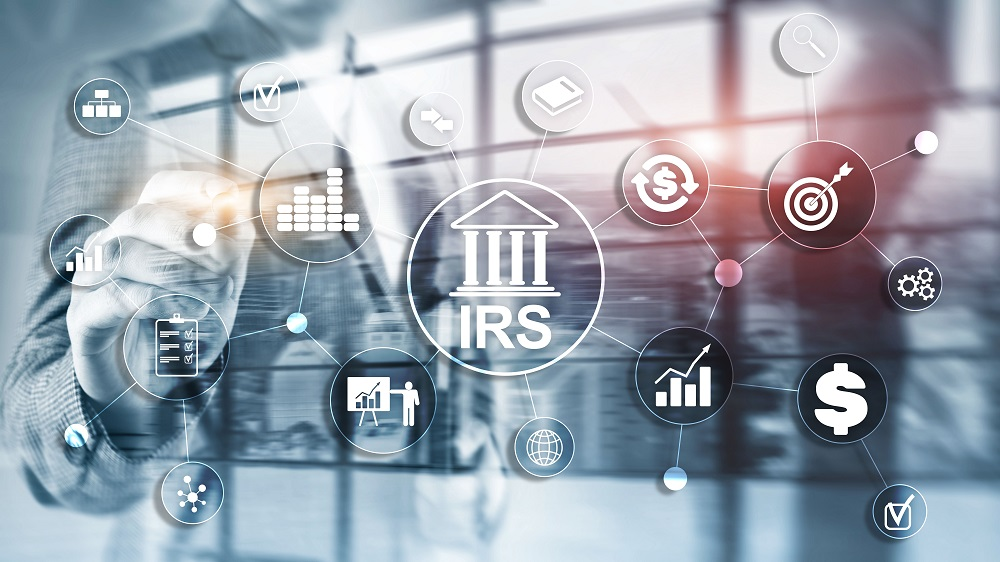 A graphic of transparent circles with images of graphs, dollar signs, etc. and one larger main circular graphic with a white icon of a Greek temple that says IRS in the middle. In the bluish grey background is a photo of a business man and woman, with the man seeming to touch the circles in the foreground, posing the question, Can the IRS take my personal injury settlement.