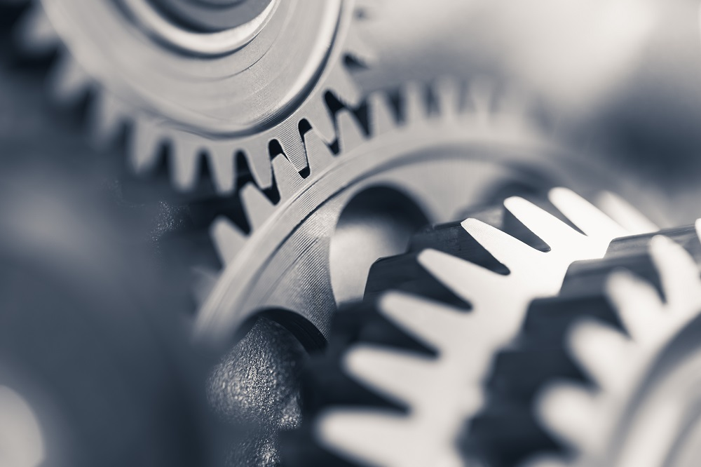 Steel gears rotating in unison, positing the question, How does personal injury law work in Philadelphia?