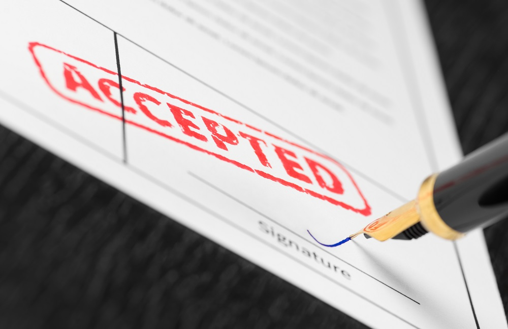 A white piece of paper is a form with ACCEPTED stamped on it in red while a gold-tipped pen is signing in blue ink, positing the question, Should I accept a personal injury offer in Philadelphia?
